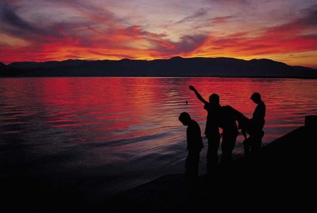 Местная ребятня ловит рыбу с берега без удилищ